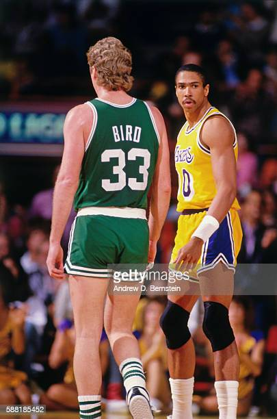 Mychal Thompson of the Los Angeles Lakers looks on with Larry Bird of the Boston Celtics during a game circa 1987 at The Forum in Los Angeles...