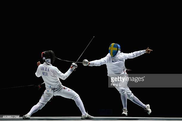 Myeongki Kim of Korea and Linus Islas Flygare of Sweden compete in Fencing Mixed Continental Team Bronze Medal Bout on day four of the Nanjing 2014...