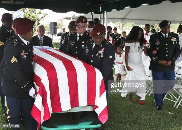 Myeshia Johnson is escorted to her seat as a Military Honor Guard carries the casket of her husband US Army Sgt La David Johnson during his burial...