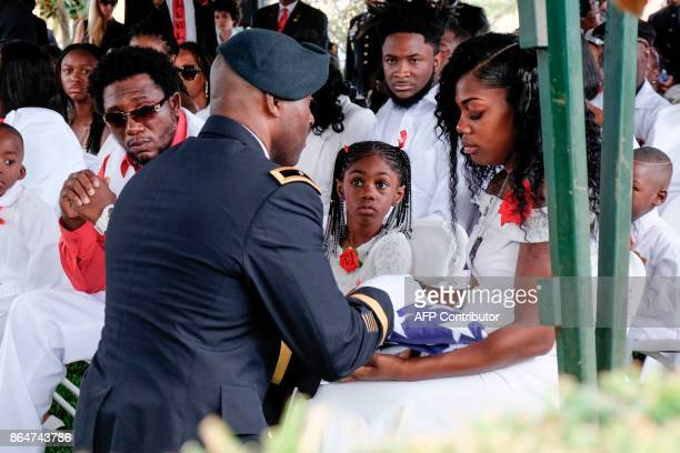 Myeshia Johnson is presented with a folded US flag by a military honor guard member during the burial service for her husband US Army Sgt La David...