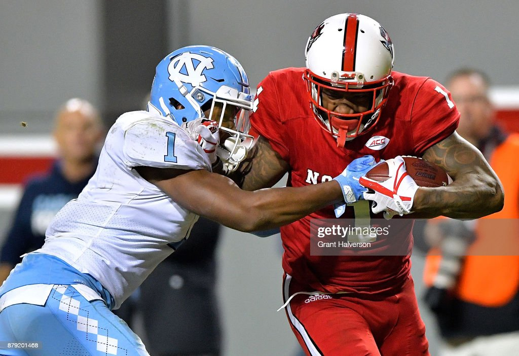 Myles Dorn #1 of the North Carolina Tar Heels tackles Jaylen Samuels #1 of the North Carolina State Wolfpack during their game at Carter Finley Stadium on November 25, 2017 in Raleigh, North Carolina. North Carolina State won 33-21.