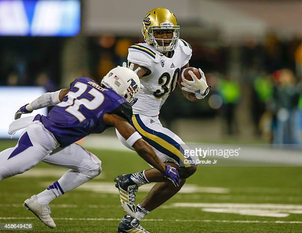 Myles Jack of the UCLA Bruins rushes for a touchdown against Budda Baker of the Washington Huskies in the second quarter on November 8 2014 at Husky...