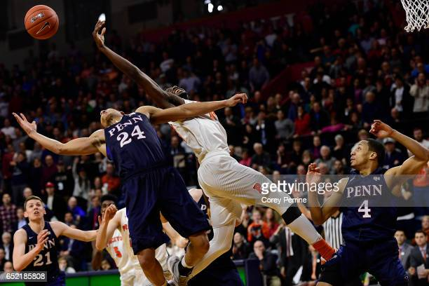 Myles Stephens of the Princeton Tigers and Matt Howard stretch for the ball as Darnell Foreman of the Pennsylvania Quakers looks on during the second...