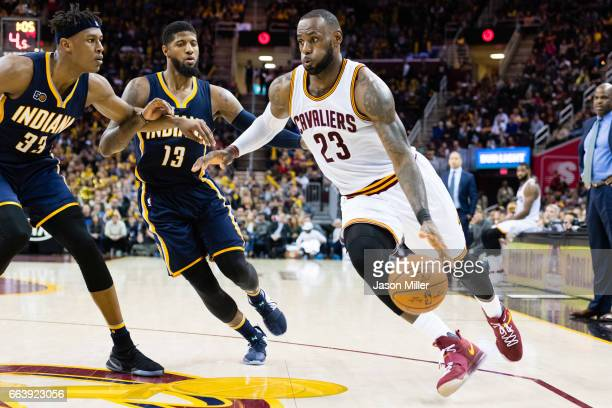 Myles Turner and Paul George of the Indiana Pacers try to stop LeBron James of the Cleveland Cavaliers during the second half at Quicken Loans Arena...