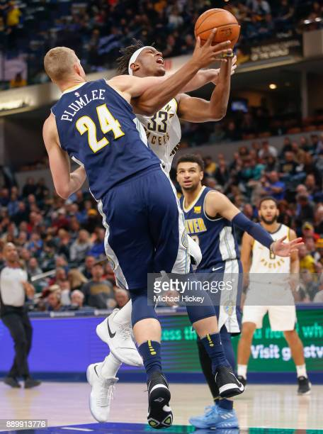 Myles Turner of the Indiana Pacers is fouled by Mason Plumlee of the Denver Nuggets while shooting at Bankers Life Fieldhouse on December 10 2017 in...
