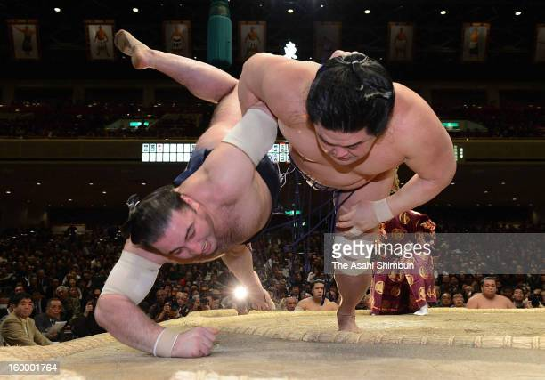 Myogiryu throws Georgian wrestler Tochinoshin whose real name is Levan Gorgadze to win during day 12 of the Grand Sumo New Year Tournament at Ryogoku...