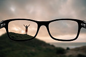Some glasses focusing a man with arms raised on top of a mountain.