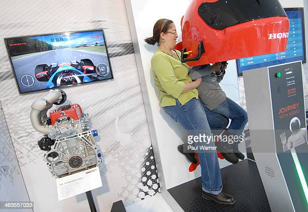Myron Hall is lifted up by his grandmother Patrese Sayas both of Southfield MI to play the Honda racing video game on day 1 of the North American...