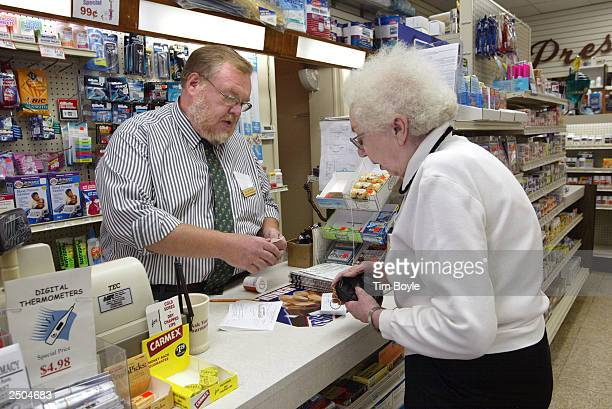 Myrtle Gosse pays pharmacist Bill Mattson for her order at Ballin Pharmacy September 17 2003 in Chicago Illinois Illinois Gov Rod R Blagojevich...