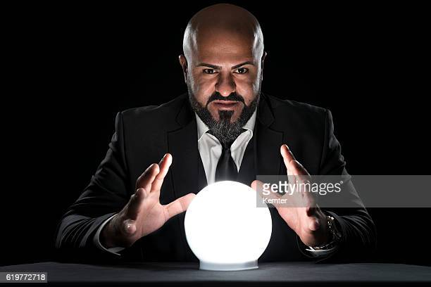 mysterious fortune teller gesturing at crystal ball