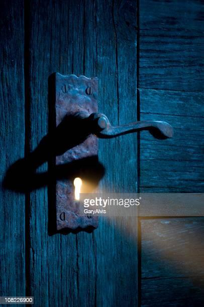 Geheimnisvollen Licht durch antike Tür mit Keyhole-Ausschnitt