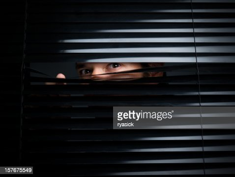 Mysterious Male Peering Out From Opening Behind Blinds
