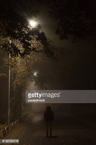 Mysterious man in the hood, alone on dark street : Stock Photo