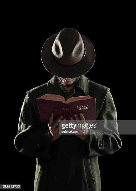 Mysterious Man Wearing Hat Reading Holy Bible In Dark