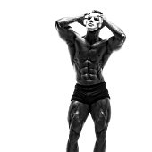 Mysterious Muscular man hiding behind white mask. Bodybuilder with white mask on his face. Studio shot on white background