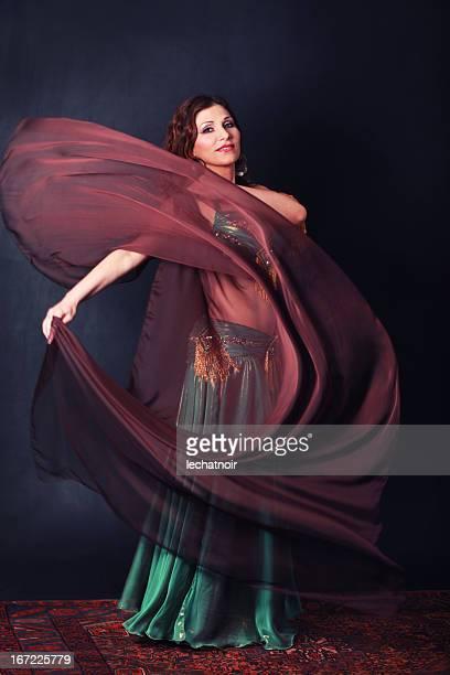 Mysterious oriental dancer swinging a silk cape