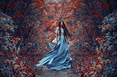 Mysterious sorceress in a beautiful blue dress. Her hair and dress are fluttering in the wind. Background bright, autumn, fiery forest with cold tones. Artistic Photography