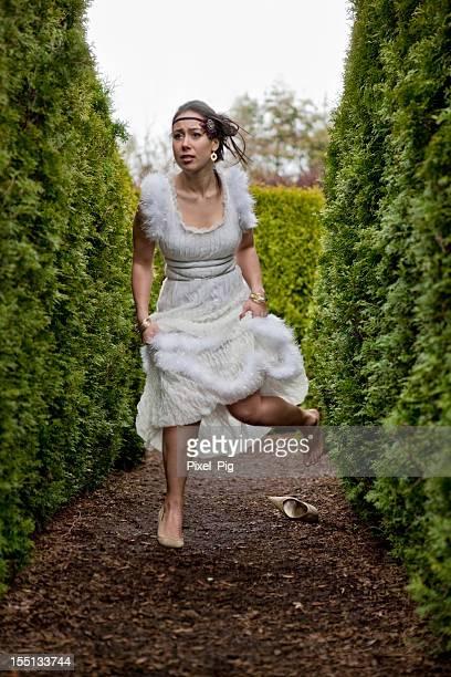Mystérieuse jeune femme en robe de vous réfugier dans un labyrinthe.