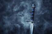 mysteriousand magical photo of silver sword over gothic snowy black background. Medieval period concept