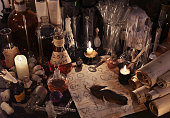 Mystic still life with old parchments papers, vintage bottles, candles, skull and magic objects. Ancient pharmacy, medieval alchemist or witch laboratory, ritual with occult and esoteric symbols