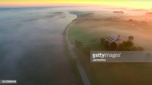 Mystique brumeux pays paysage avec rivière, de même que des fermes et des habitations.
