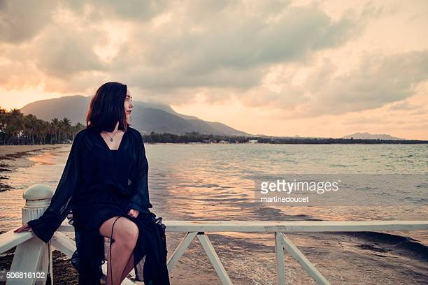 Mystical young woman sitting on a pier, sunset, enjoying nature.