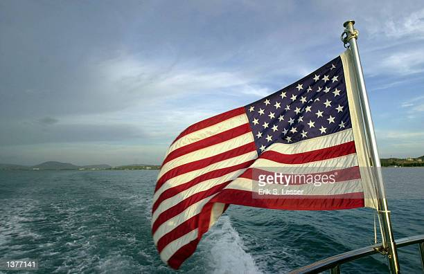 n American flag flaps in the wind aboard a ferry going between the leeward and windward parts of the Guantanamo Bay Naval Base in Cuba As the...