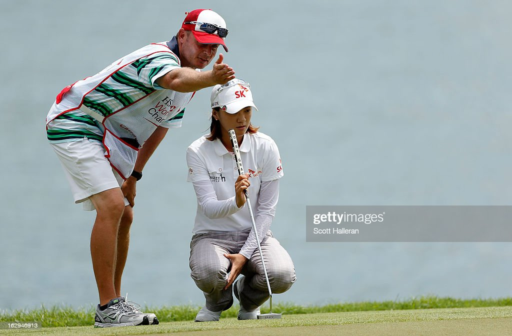 Na Yeon Choi of South Korea studies the line of a putt with her caddie Jason Hamilton during the third round of the HSBC Women's Champions at the Sentosa Golf Club on March 2, 2013 in Singapore, Singapore.