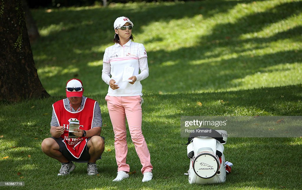 Na Yeon Choi of South Korea waits to play a shot alongside her caddie Jason Hamilton during the second round of the HSBC Women's Champions at the Sentosa Golf Club on March 1, 2013 in Singapore, Singapore.