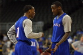 Naadir Tharpe and Tyshawn Taylor of the Kansas Jayhawks talk during practice as they prepare to face Detroit in the second round of the NCAA Men's...