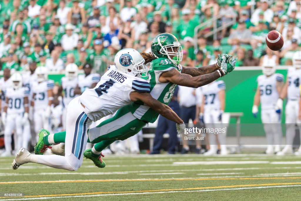 Naaman Roosevelt #82 of the Saskatchewan Roughriders just misses making a diving catch despite the coverage of Brandon Harris #4 of the Toronto Argonauts in the second half of the game between the Toronto Argonauts and Saskatchewan Roughriders at Mosaic Stadium on July 29, 2017 in Regina, Canada.