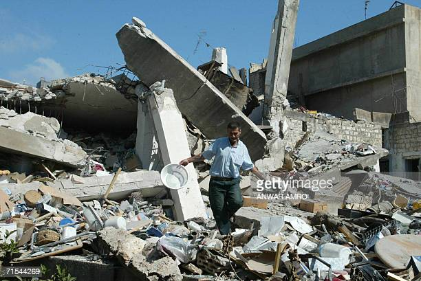 A man salvagess some belongings from the rubble of his destroyed house in the southern Lebanese town of Nabatiyeh 31 July 2006 as Israel announced a...