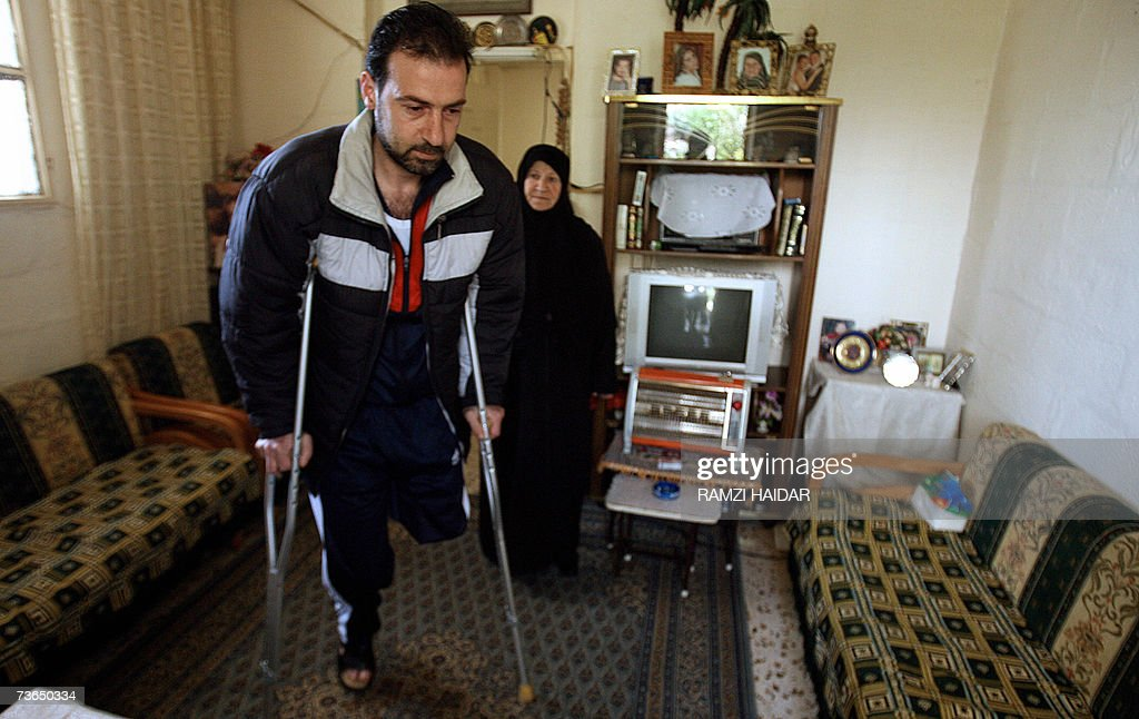 Umm Mohammed watches her son Mohammed Nahle walk on crutches to the bathroom at his home in the Lebanese southern port city of Nabatiyeh, 08 March 2007. Nahle, a Civil Defense worker, lost his leg to a cluster bomb during Israel's 34-days offensive against Lebanon's Hezbollah militants. Prosthetic limb-fitting centres in southern Lebanon are struggling to cope with the rising toll from the one million unexploded munitions left over from last year's war with Israel.