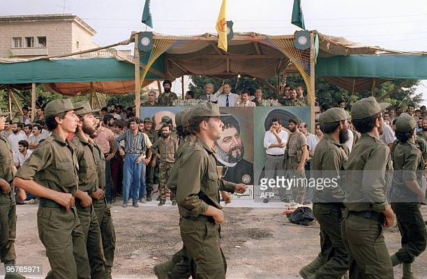 Nabih Berri reviews militiamen from his Amal movement as they parade 08 August 1986 in front of Imam Moussa Al Sadr portrait in the southern suburb...