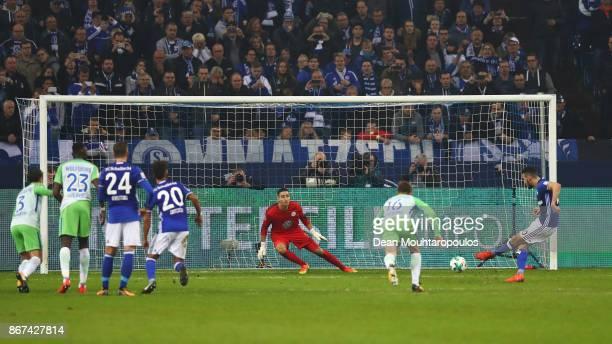 Nabil Bentaleb of Schalke 04 shoots and scores a penalty goal past Goalkeeper Koen Casteels of Wolfsburg during the Bundesliga match between FC...