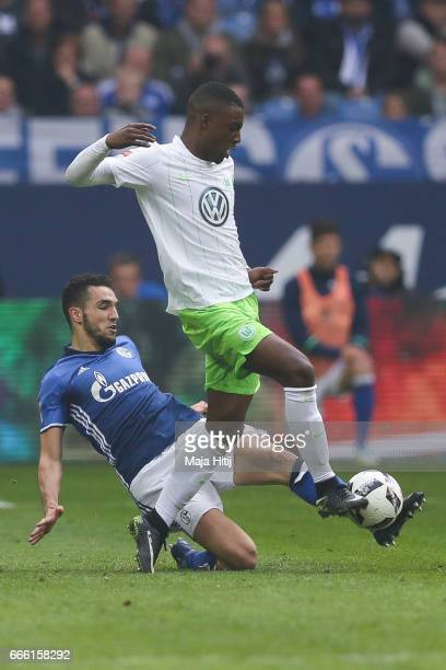 Nabil Bentaleb of Schalke and Richedly Bazoer of Wolfsburg battle for the ball during the Bundesliga match between FC Schalke 04 and VfL Wolfsburg at...