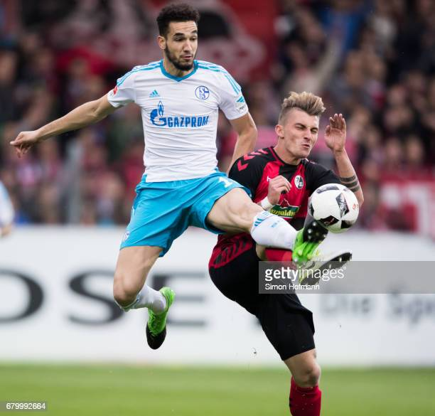 Nabil Bentaleb of Schalke is challenged by Maximilian Philipp of Freiburg during the Bundesliga match between SC Freiburg and FC Schalke 04 at...