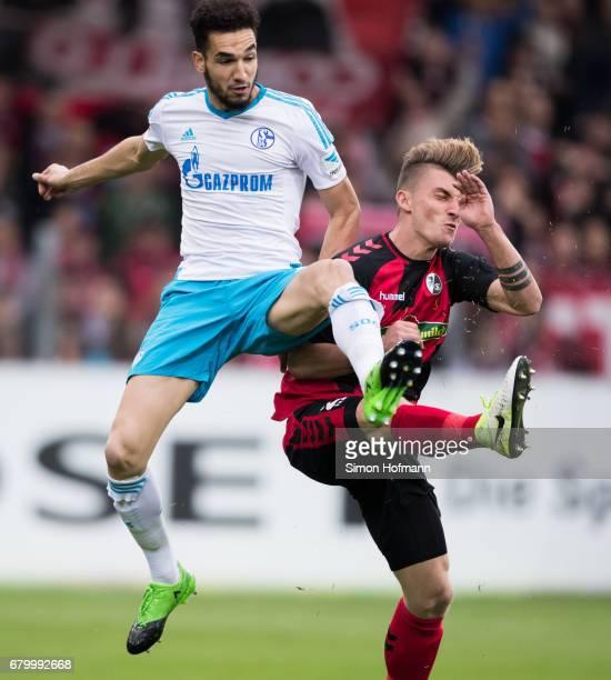 Nabil Bentaleb of Schalke is challenged by Maximilian Philipp of Freiburg during the Bundesliga match between SC Freiburg and FC Schalke 04 at...