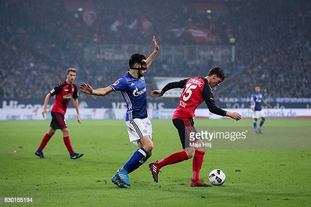 Nabil Bentaleb of Schalke is challenged by Pascal Stenzel of Freiburg during the Bundesliga match between FC Schalke 04 and SC Freiburg at...