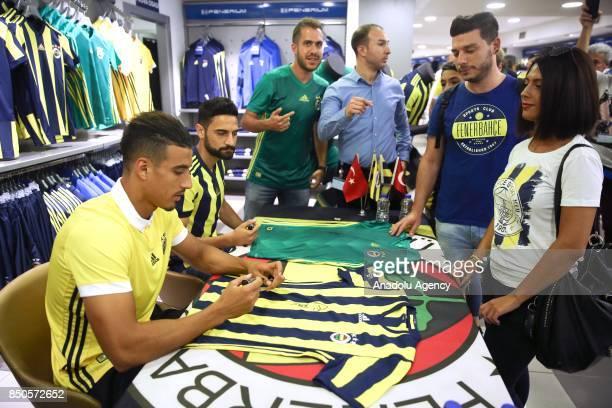 Nabil Dirar and Mehmet Ekici of Fenerbahce sign fan jerseys at the Fenerbahce Ulker Stadium Fenerium store in Istanbul Turkey on September 21 2017
