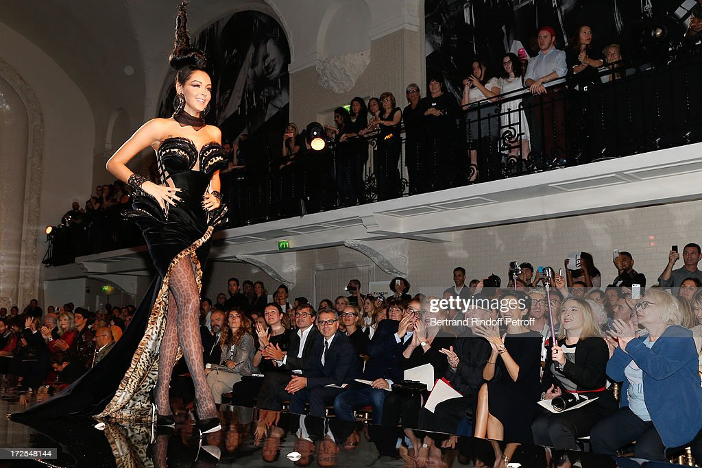 Nabilla Benattia walks on the catwalk, owners of Gaultier Manuel and Marc Puig, Gilles Dufour, <a gi-track='captionPersonalityLinkClicked' href=/galleries/search?phrase=Catherine+Deneuve&family=editorial&specificpeople=123833 ng-click='$event.stopPropagation()'>Catherine Deneuve</a>, Jean-Paul Goude, <a gi-track='captionPersonalityLinkClicked' href=/galleries/search?phrase=Farida+Khelfa&family=editorial&specificpeople=4866090 ng-click='$event.stopPropagation()'>Farida Khelfa</a> and <a gi-track='captionPersonalityLinkClicked' href=/galleries/search?phrase=Josiane+Balasko&family=editorial&specificpeople=768143 ng-click='$event.stopPropagation()'>Josiane Balasko</a> near her daughter <a gi-track='captionPersonalityLinkClicked' href=/galleries/search?phrase=Marilou+Berry&family=editorial&specificpeople=672535 ng-click='$event.stopPropagation()'>Marilou Berry</a> attend the Jean Paul Gaultier show as part of Paris Fashion Week Haute-Couture Fall/Winter 2013-2014 at 325 Rue Saint Martin on July 3, 2013 in Paris, France.