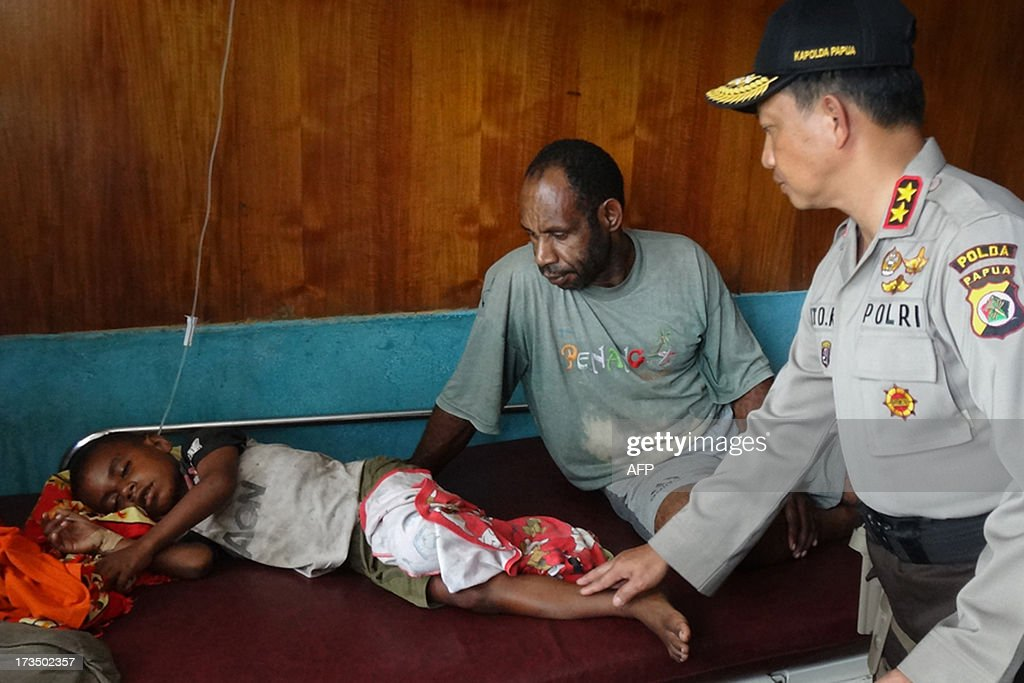 Nabire town police chief Senior Commissioner Bahara Marpaung (R) visits a Papuan boy at a hospital on July 15, 2013 who was injured from a stampede in a boxing stadium. Seventeen spectators were crushed to death and another 38 were injured at a boxing match in remote eastern Indonesia province of Papua after supporters of the loser started a riot, police said Monday.