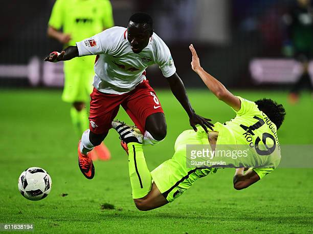 Naby Deco Keita of Leipzig is challenged by JaCheol Koo of Augsburg during the Bundesliga match between RB Leipzig and FC Augsburg at Red Bull Arena...
