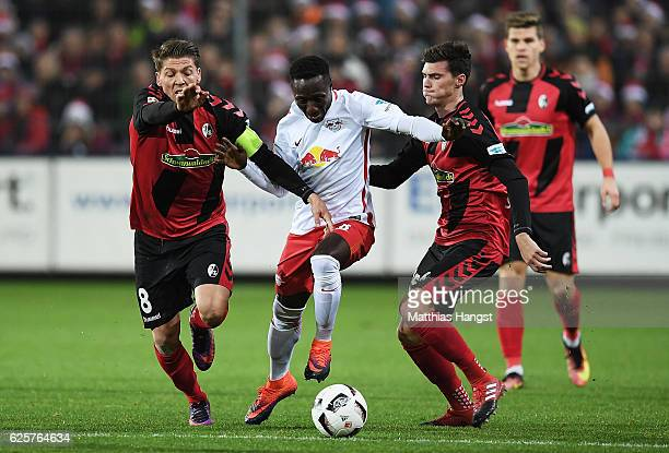Naby Deco Keita of RB Leipzig is challenged by Mike Frantz of SC Freiburg during the Bundesliga match between SC Freiburg and RB Leipzig at...