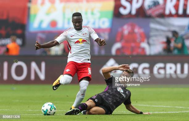 Naby Keita of Leipzig and Florian Niederlechner of Freiburg vie during the Bundesliga match between RB Leipzig and SportClub Freiburg at Red Bull...