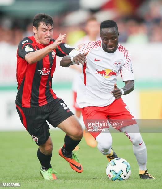 Naby Keita of Leipzig is challenged by Daniel Nietzer of Dorfmerkingen during the DFB Cup first round match between Sportfreunde Dorfmerkingen and RB...