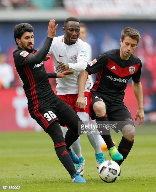 Naby Keita of RB Leipzig is challenged by Almog Cohen and Stefan Lex of FC Ingolstadt 04 during the Bundesliga match between RB Leipzig and FC...
