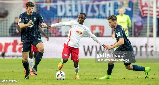 Naby Keita of RB Leipzig is challenged by Mario Gomez of VfL Wolfsburg and Yannick Gerhardt of VfL Wolfsburg during the Bundesliga match between RB...
