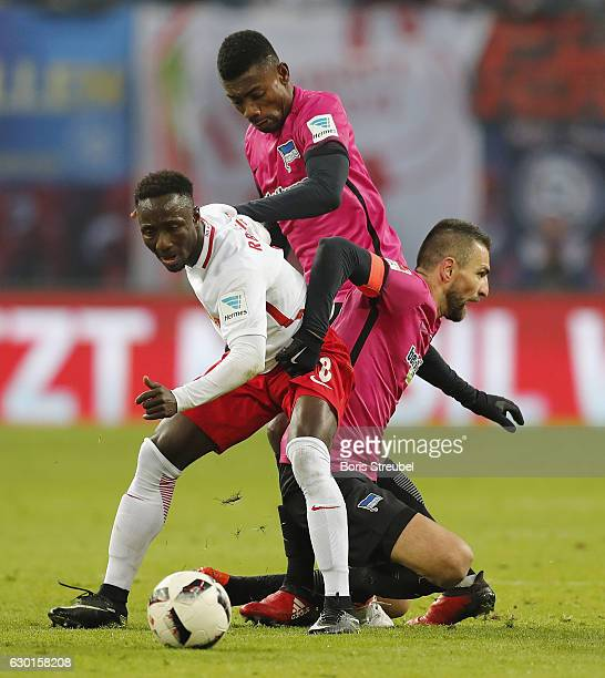 Naby Keita of RB Leipzig is challenged by Salomon Kalou and Vedad Ibisevic of Hertha BSC during the Bundesliga match between RB Leipzig and Hertha...