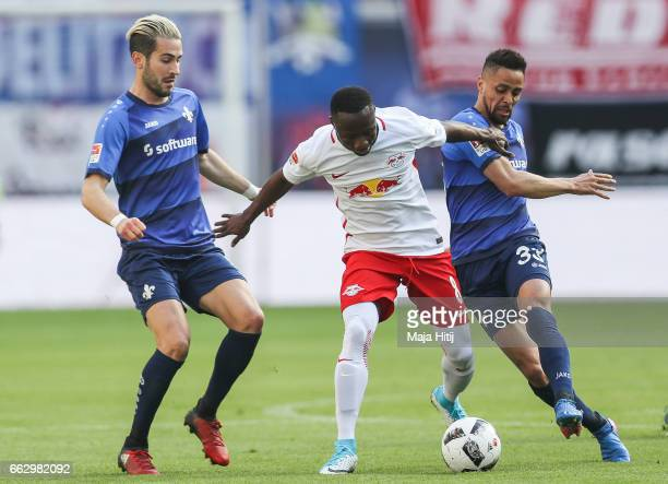 Naby Keitab of Leipzig battle for the ball with Mario Vrancic and Sam Sidney of Darmstadt during the Bundesliga match between RB Leipzig and SV...